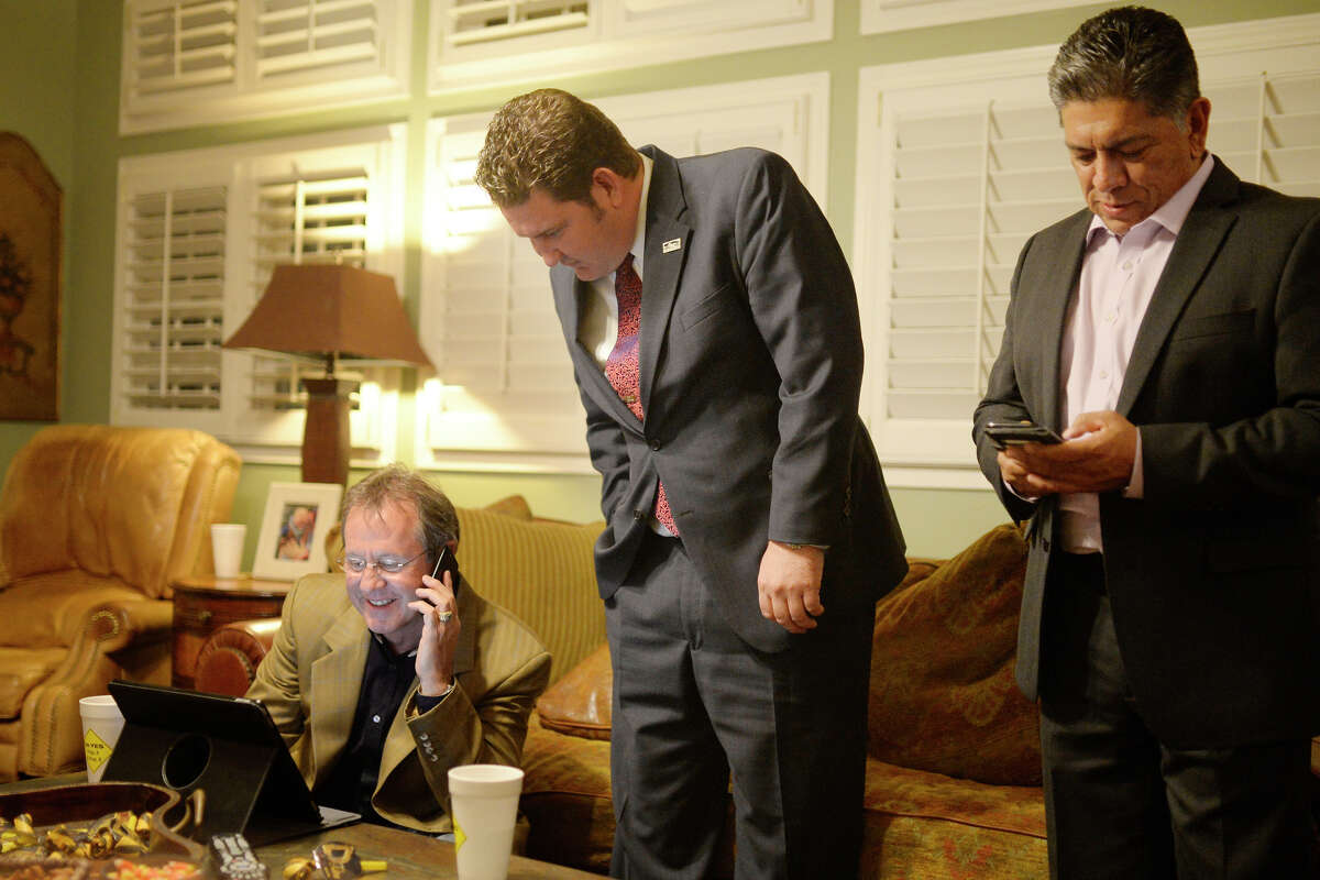 Midland Development Corp. board chairman Brent Hilliard, from left, city councilman J.Ross Lacy and city mayor Jerry Morales look over early voting results in favor of the proposed road bond on Nov. 7 at an election results party.
