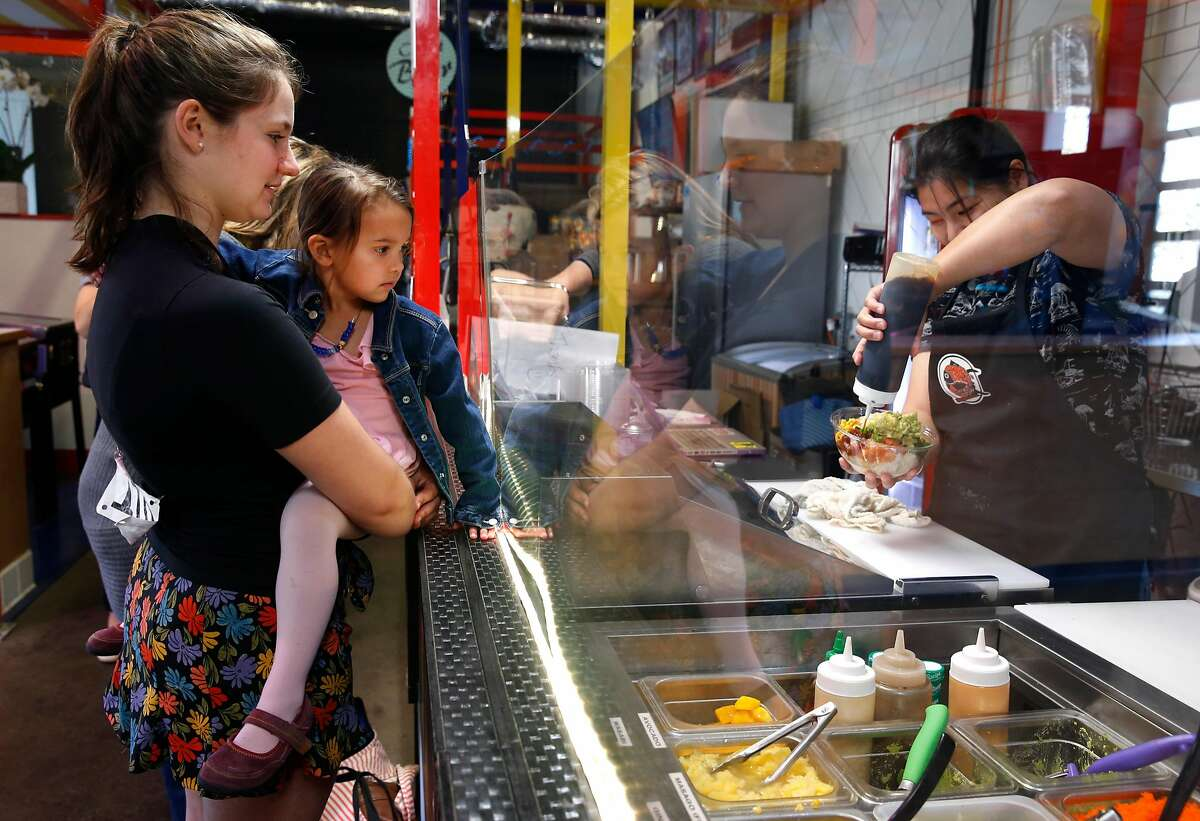 Katie Spegar and Dahlia Tarou, 4, watch their lunch orders being prepared at the Poke Delish stand inside The Myriad incubator space for start-up restaurants on the ground floor of a new residential building at Market and 15th streets in San Francisco, Calif. on Saturday, Nov. 11, 2017.