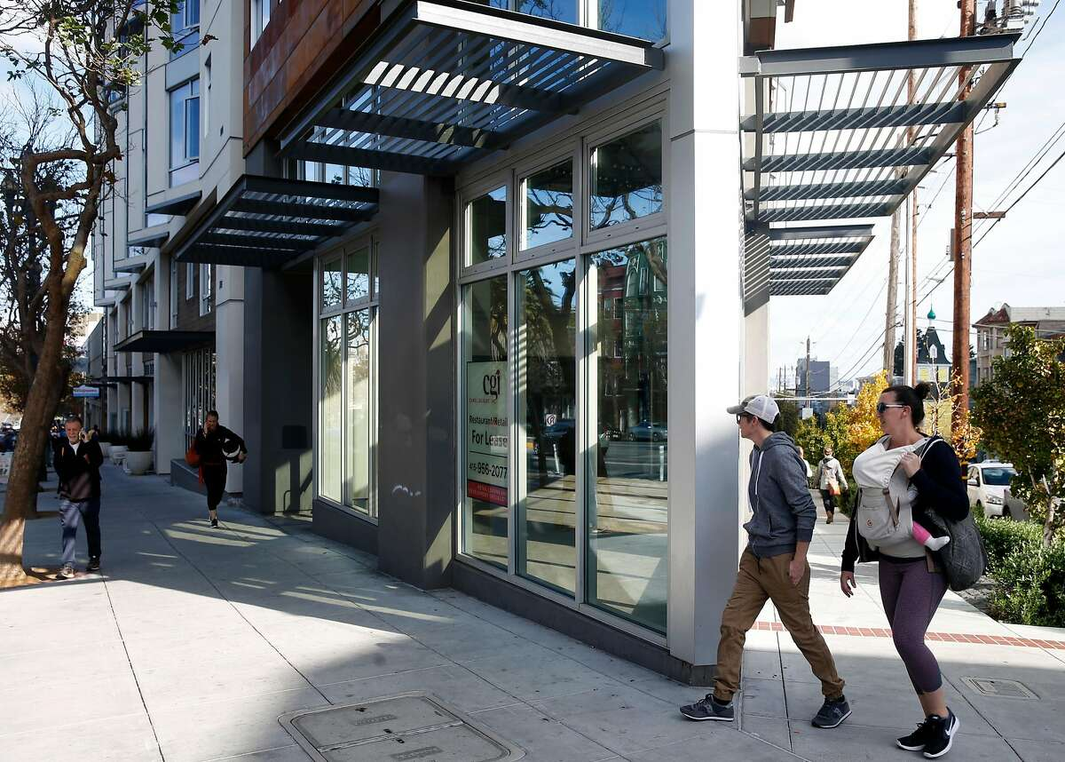 People walk past a vacant restaurant space on a corner location of a new residential building at Market and 15th streets in San Francisco, Calif. on Saturday, Nov. 11, 2017.