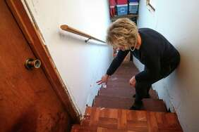 Katie Reed points to leftover damage in the stairway leading up to a room above her garage while recounting when she came face to face with an 8-point deer in her garage on Monday, Nov. 20, 2017, in the Imperial Oaks subdivision of Spring.
