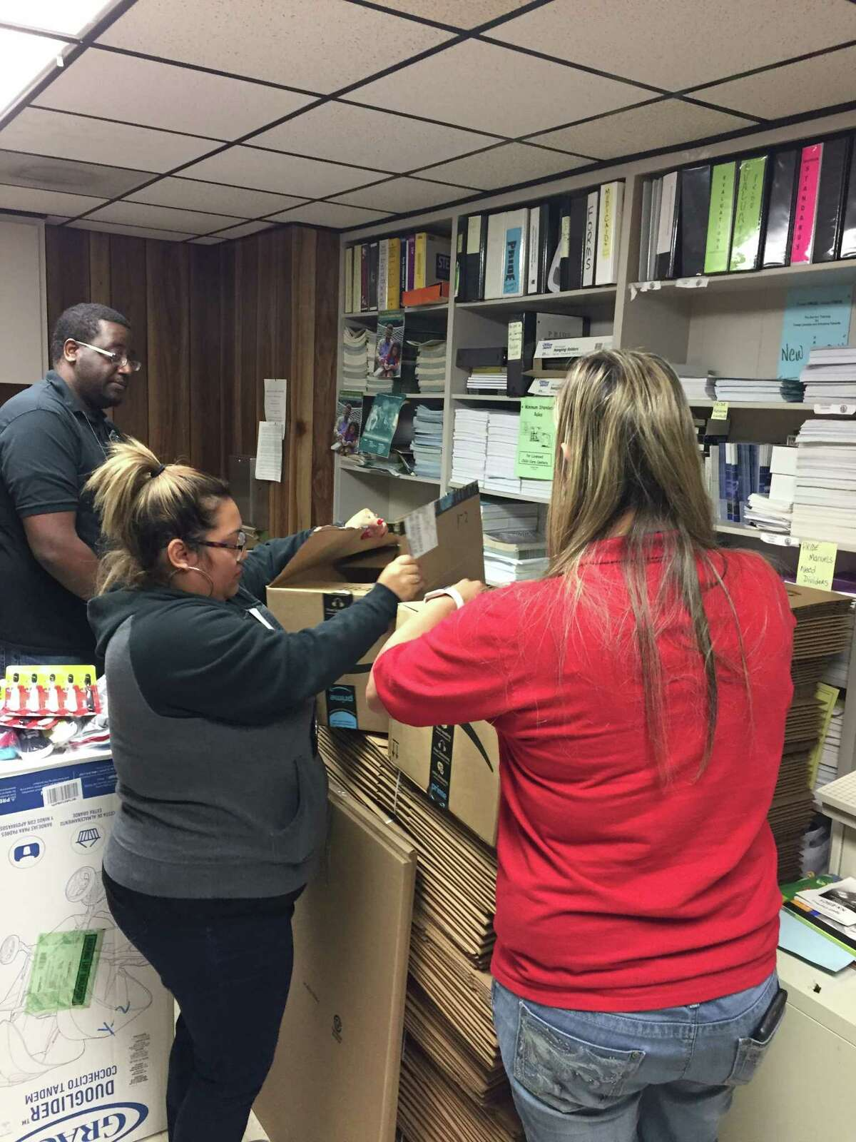 Program director Alfred Bryant works with administrative assistants Wendy Cartagena, center, and Tara Aquila tounpack boxes of gifts at the Rosenberg office of the Texas Department of Family Services.