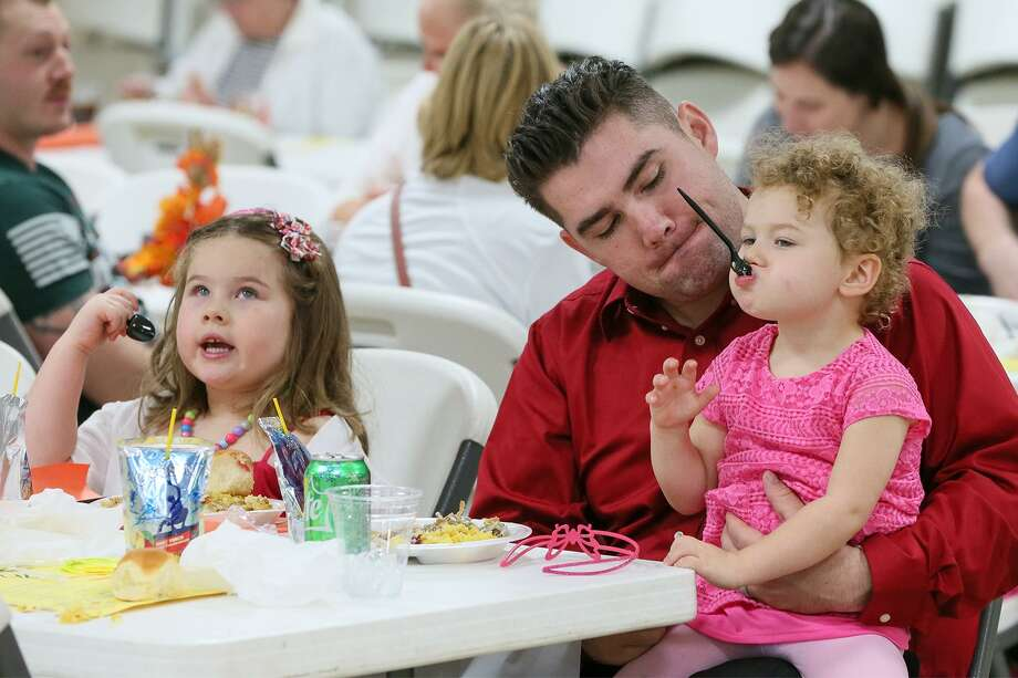 Ashton Hood enjoys a meal with his two daughters, Stella (right), 2, and Ava, 5, at the 2nd Annual Giving Back Thanksgiving Military Dinner at VFW Post 8315, 1000 FM 78 in Schertz, on Sunday, Nov. 19, 2017. Photo: Marvin Pfeiffer / San Antonio Express-News / Express-News 2017