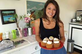 Alyssa DeMatteo, owner of Wildflour Confections in Seymour, Conn., holds a plate of her pumpkin spice and French toast cupcakes.