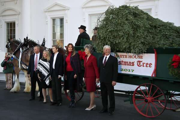 First lady Melania Trump, third from right, with her son Barron Trump, third from left, is presented by the Chapman family of Silent Night Evergreens, the Wisconsin-grown Christmas Tree at the North Portico of the White House in Washington, Monday. The tree will be displayed in the White House Blue Room.