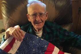Claude Pruett with his quilt made by Barbt Lambert, a member of First Baptist Church