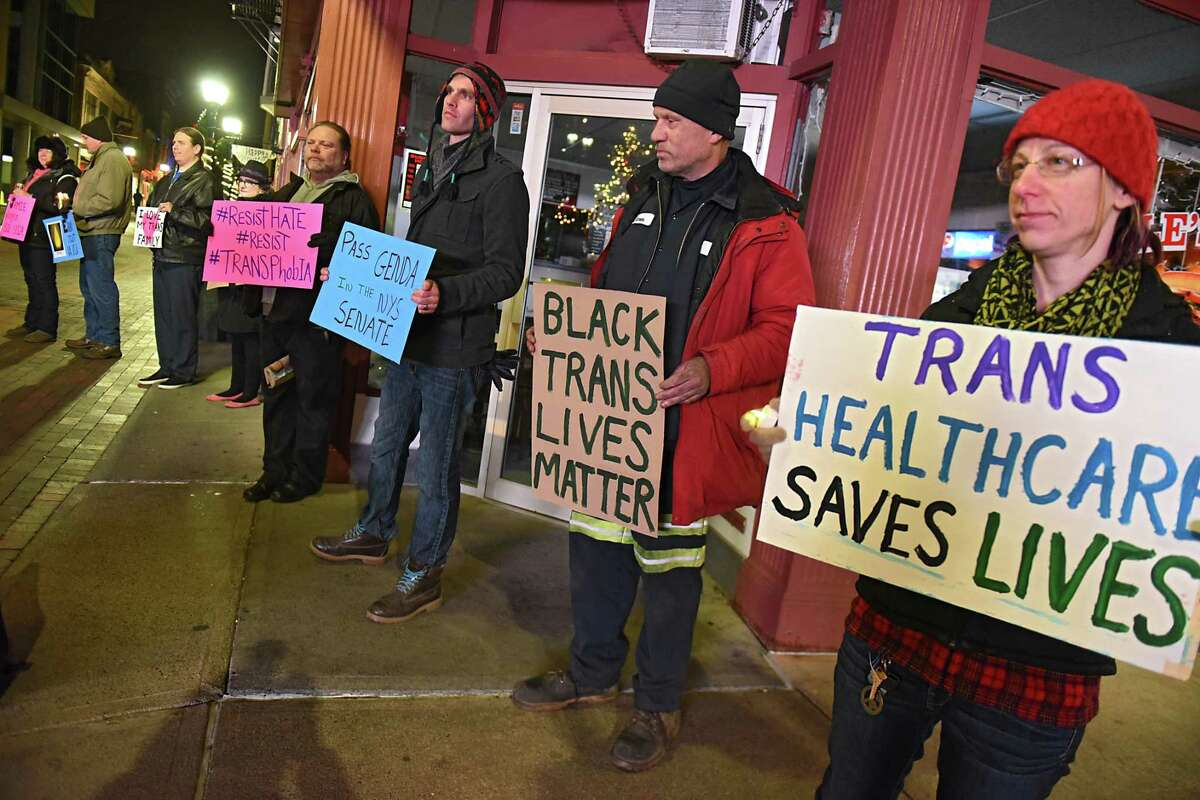 People hold signs on Jay St. on Transgender Day of Remembranceon Monday, Nov. 20, 2017 in Schenectady, N.Y.