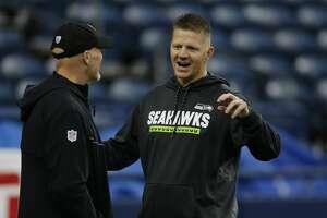 Atlanta Falcons head coach Dan Quinn, left, talks with Seattle Seahawks offensive coordinator Darrell Bevell before an NFL football game, Monday, Nov. 20, 2017, in Seattle. (AP Photo/Stephen Brashear)