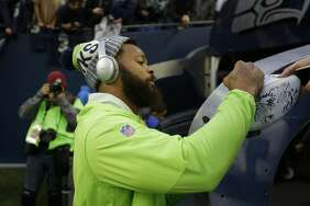 Seattle Seahawks' Michael Bennett signs autographs before an NFL football game, Monday, Nov. 20, 2017, in Seattle. (AP Photo/Ted S. Warren)