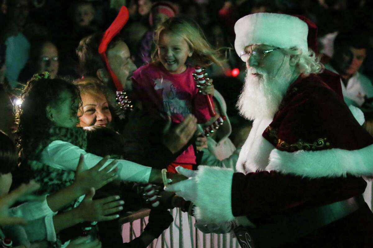 Santa shakes hands with fans during the Lighting of the Doves event on Saturday, Nov. 18, 2017, at Town Green Park.