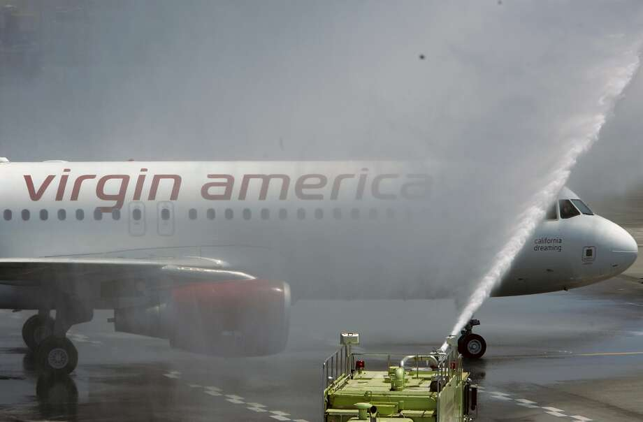 VIRGIN09_137_MBK.JPG Two Virgin America planes taxi to their terminal, under ceremonial water spray, where a reception party awaits passengers to mark the launch of the first flights by Virgin America, the new, based-in-San Francisco low fare airline created by Virgin's Richard Branson, at SFO in San Francisco, CA, on Wednesday, August, 8, 2007. photo taken: 8/8/07 Mike Kane / The Chronicle    * Photo: MIKE KANE, SFC