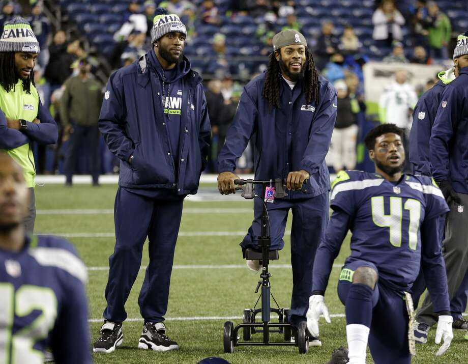 Seattle Seahawks Kam Chancellor, left, and Richard Sherman, both out injured, look on at teammates stretching before an NFL football game against the Atlanta Falcons, Monday, Nov. 20, 2017, in Seattle. (AP Photo/Ted S. Warren) Photo: Ted S. Warren/AP