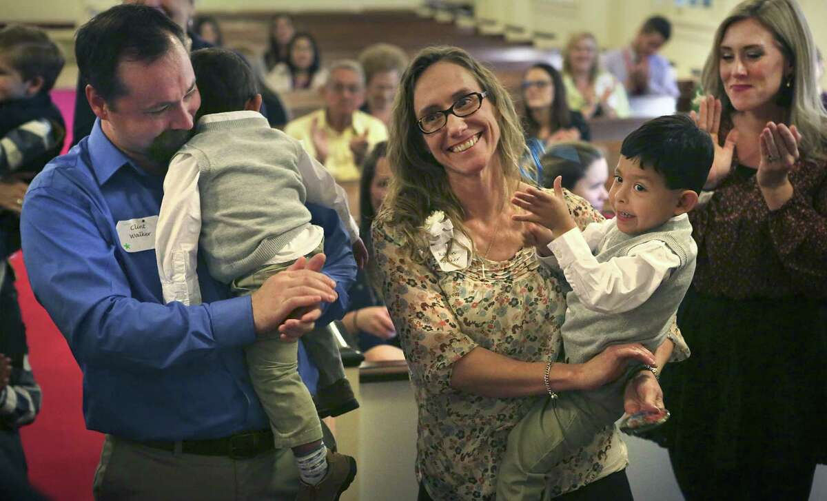 Karen Walker (center) holds her newly adopted son, 19-month-old Antonio Walker, while her husband, Clint Walker (left), holds 3-year-old Jose Walker. Onlookers clapped after the boys' adoptions were announced at a Texas Department of Family and Protective Services adoption day event at the First Presbyterian Church in Seguin on Monday. At right is Jordan Underwood, Karen's niece.