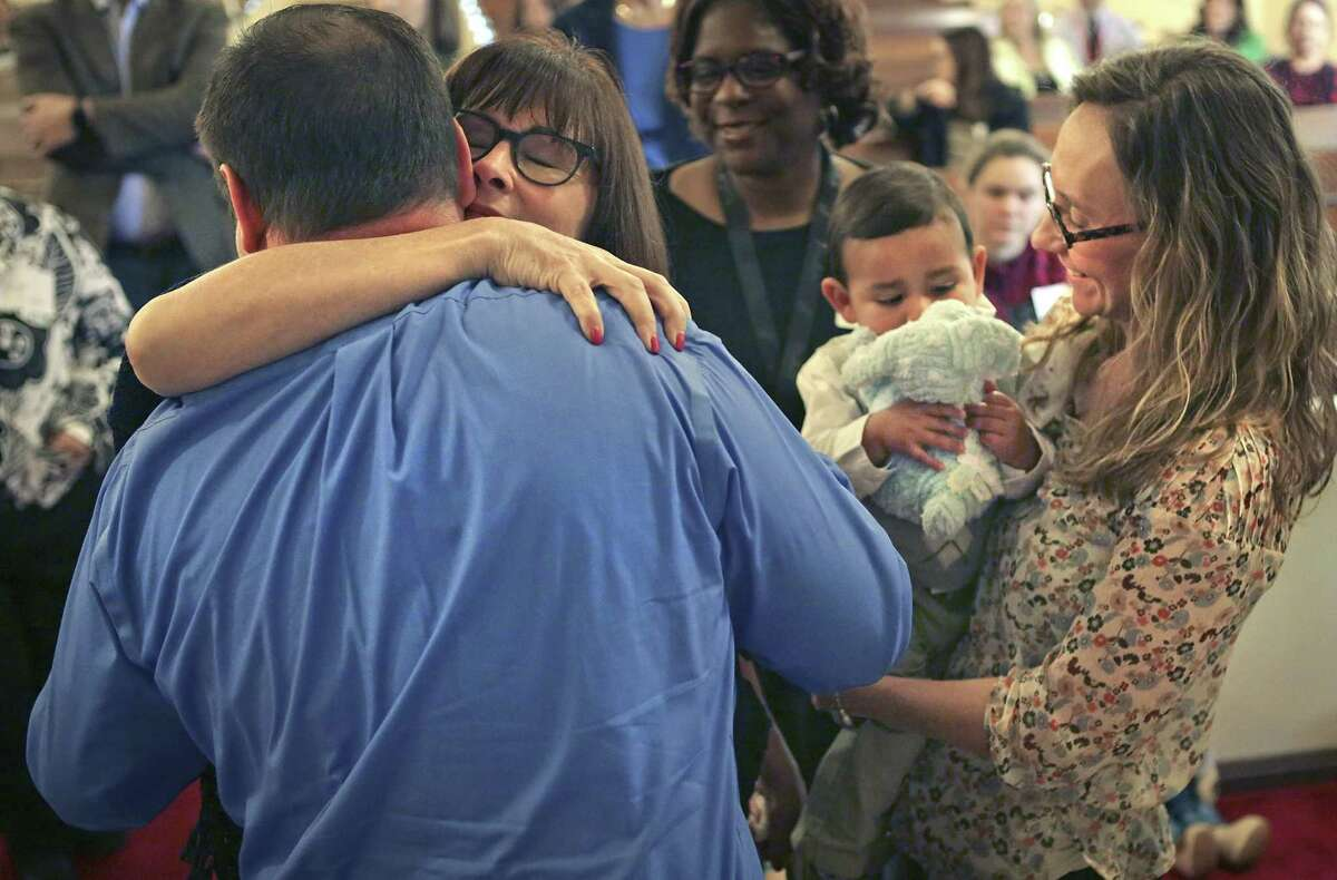 Donna Couch hugs her son, Clint Walker (left), as his wife, Karen Walker, holds one of the couple's two adopted sons, 19-month-old Antonio Walker. The Walkers formally adopted the two boys Monday at a Texas Department of Family and Protective Services adoption day ceremony at the First Presbyterian Church in Seguin. The family lives in San Antonio.
