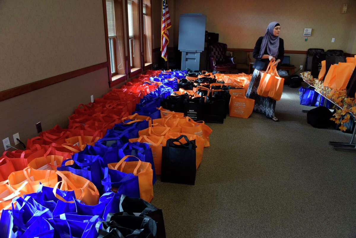 Uzma Popal, nutrition outreach and education program coordinator for Unity House, carries bags containing food items to deliver to families at the Thanksgiving Food Package Distribution put on by CEO, Unity House and Capital Roots on Monday, Nov. 20, 2017, in Troy, N.Y. The three local non-profits hold the yearly event to to get items out to 300 households so that they can prepare and serve a Thanksgiving meal to their family. (Paul Buckowski / Times Union)