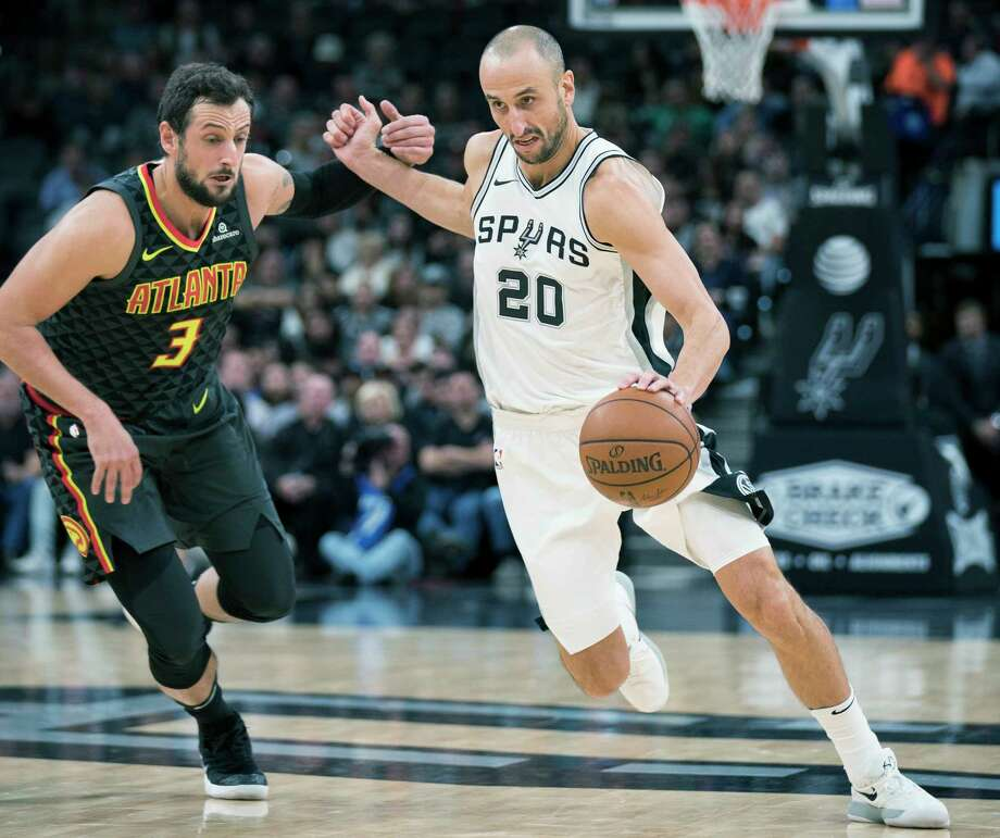 San Antonio Spurs guard Manu Ginobili (20), of Argentina, drives around Atlanta Hawks forward Marco Belinelli, of Italy, during the first half of an NBA basketball game, Monday, Nov. 20, 2017, in San Antonio. (AP Photo/Darren Abate) Photo: Darren Abate, Associated Press / FR115 AP