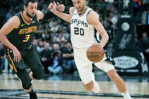 San Antonio Spurs guard Manu Ginobili (20), of Argentina, drives around Atlanta Hawks forward Marco Belinelli, of Italy, during the first half of an NBA basketball game, Monday, Nov. 20, 2017, in San Antonio. (AP Photo/Darren Abate)