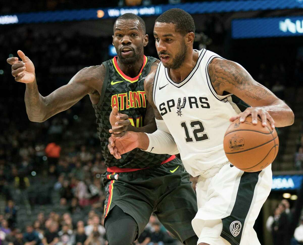 San Antonio Spurs forward LaMarcus Aldridge (12) drives around Atlanta Hawks center Dewayne Dedmon during the first half of an NBA basketball game, Monday, Nov. 20, 2017, in San Antonio. (AP Photo/Darren Abate)