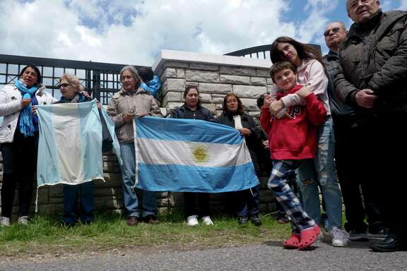 People gather outside the Naval base in Mar del Plata, Argentina, Monday, Nov. 20, 2017. The Argentine submarine ARA San Juan has been lost at sea for five days with 44 crew members on board as it was on a voyage from the extreme southern port of Ushuaia to the city of Mar del Plata. (AP Photo/Paul Byrne)
