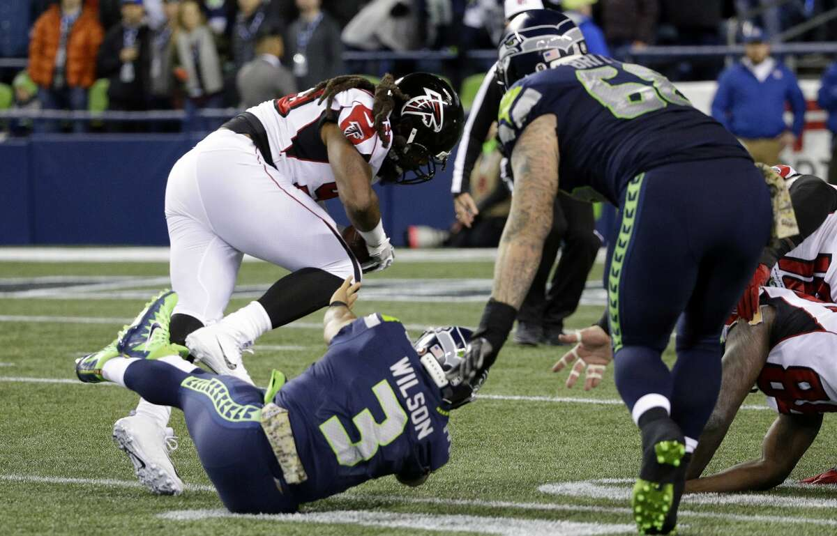 Atlanta Falcons' Adrian Clayborn races away with the ball for a touchdown after scooping up a fumble by Seattle Seahawks quarterback Russell Wilson (3) after Wilson was sacked in the first half of an NFL football game, Monday, Nov. 20, 2017, in Seattle. (AP Photo/Ted S. Warren)