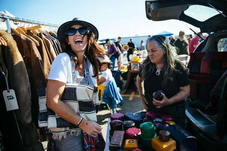 Jeni Maus shares a laugh with Daphne Schrampf of Made in the Motherland, at the Alameda Flea Market in Alameda, Calif. Sunday, October 1, 2017.