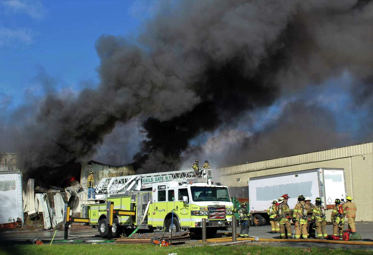 Firefighters work at the scene of of a fire Monday, Nov. 20, 2017, at the Verla International cosmetics factory on Temple Hill Road in New Windsor, N.Y. Authorities say two explosions and a fire at the cosmetics factory in the Hudson Valley have left numerous people injured, including firefighters caught in the second blast. (Jerry Barao via AP) ORG XMIT: NYCL100