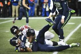 SEATTLE, WA - NOVEMBER 20: Tight end Luke Willson #82 of the Seattle Seahawks is tackled by defensive tackle Grady Jarrett #97 of the Atlanta Falcons for a loss of 4 yards during a fake field goal attempt during the second quarter of the game at CenturyLink Field on November 20, 2017 in Seattle, Washington.  (Photo by Steve Dykes/Getty Images)
