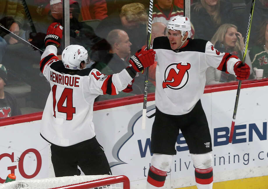 New Jersey Devils' John Moore, right, and Adam Henrique celebrate Moore's winning goal in overtime off Minnesota Wild goalie Devan Dubnyk in an NHL hockey game Monday, Nov. 20, 2017, in St. Paul, Minn. The Devils won 4-3. (AP Photo/Jim Mone) ORG XMIT: MNJM110 Photo: Jim Mone / Copyright 2017 The Associated Press. All rights reserved.