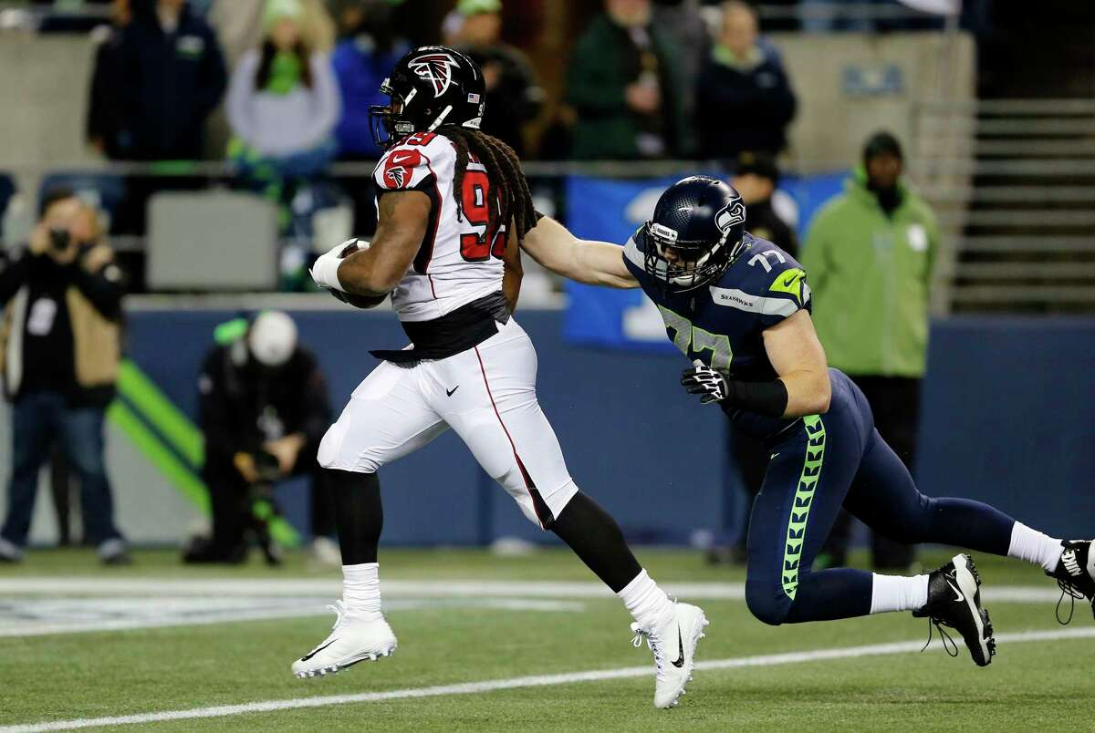 Atlanta Falcons' Adrian Clayborn (99) runs in for a touchdown as Seattle Seahawks' Ethan Pocic gives chase after Clayborn scooped up a Seahawks' fumble in the first half of an NFL football game, Monday, Nov. 20, 2017, in Seattle. (AP Photo/Stephen Brashear) ORG XMIT: SE116