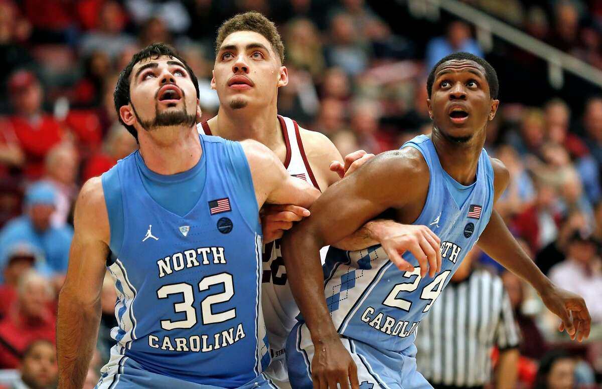 North Carolina's Luke Maye (32) and Kenny Williams (24) box out Stanford's Reid Travis in 1st half during Men's college basketball game at Maples Pavilion in Stanford, Calif., on Monday, November 20, 2017.