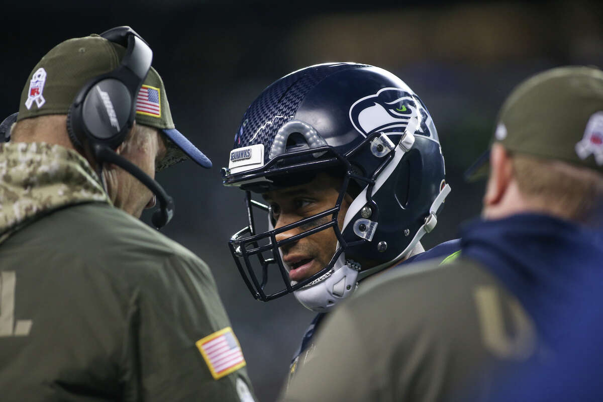Seahawks quarterback Russell Wilson talks with offensive coordinator Darrell Bevell in the second half against the Falcons at CenturyLink Field on Monday, Nov. 20, 2017.