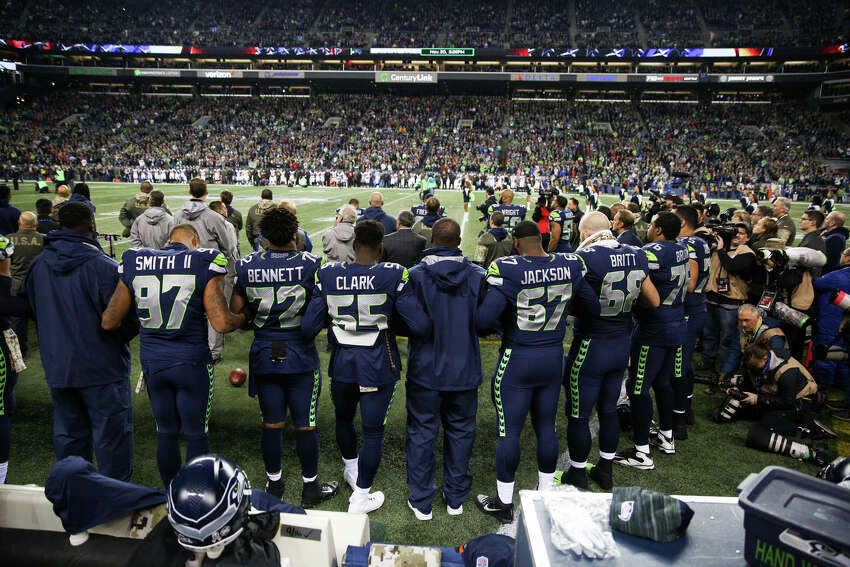 The Seahawks link arms and stand for the national anthem on their military appreciation day before playing the Falcons at CenturyLink Field on Monday, Nov. 20, 2017. No Seahawks knelt in protest of police brutality.