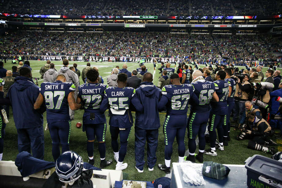 The Seahawks link arms and stand for the national anthem on their military appreciation day before playing the Falcons at CenturyLink Field on Monday, Nov. 20, 2017. No Seahawks knelt in protest of police brutality. Photo: GRANT HINDSLEY, SEATTLEPI.COM / SEATTLEPI.COM