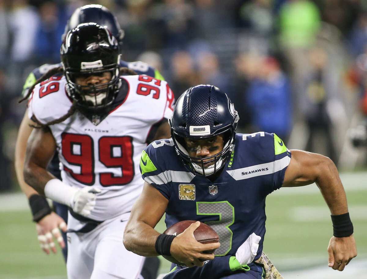 Seahawks quarterback Russell Wilson runs the ball as Falcons defensive end Adrian Clayborn gives chase at CenturyLink Field on Monday, Nov. 20, 2017.