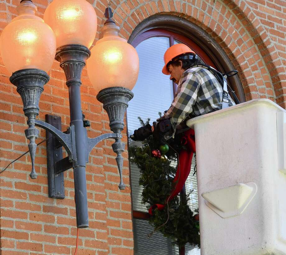 Michael Konkel, of the Saratoga Springs Department of Public Works, decorates City Hall on Tuesday.  Photo: Skip Dickstein / Times Union