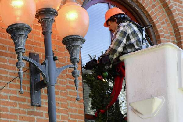 Michael Konkel, of the Saratoga Springs Department of Public Works, decorates City Hall on Tuesday.