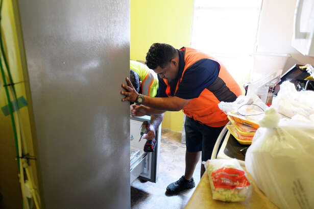 Adam Martinez, with Conns HomePlus, sets up a new donated refrigerator at the Evans family home on South 7th Street in Beaumont. The Evans family has dealt with difficulties recently, including flooding during Tropical Storm Harvey, the loss of their business and wife, Jamie, being on dialysis.  Photo taken Monday 11/20/17 Ryan Pelham/The Enterprise