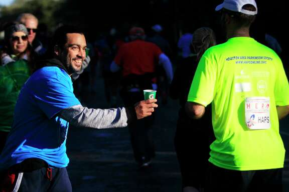 A volunteer distributes water as runners head up Montrose during the  Aramco Houston Half  Marathon.A volunteer distributes water as runners head up Montrose during the  Aramco Houston Half  Marathon.