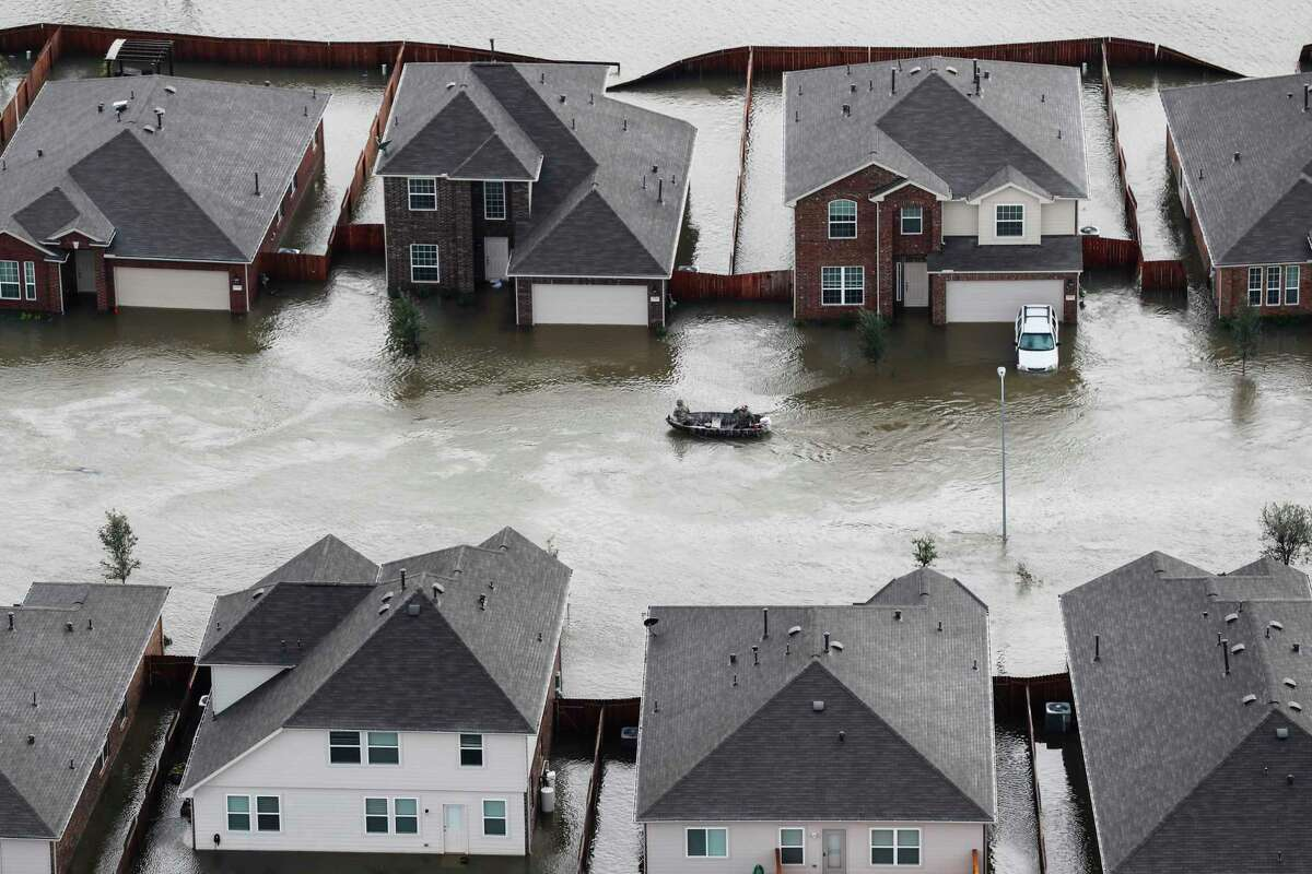 A boat runs past houses flooded by Tropical Storm Harvey on Tuesday, Aug. 29, 2017, in Spring. ( Brett Coomer / Houston Chronicle )