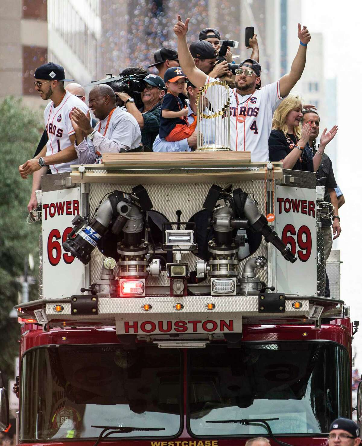 Houston Astros shortstop Carlos Correa, left, Mayor Sylvester Turner, center, and center fielder George Springer (4) wave to the crowd while riding on a ladder truck during the Astros World Series championship celebration parade on Friday, Nov. 3, 2017, in Houston. ( Brett Coomer / Houston Chronicle )