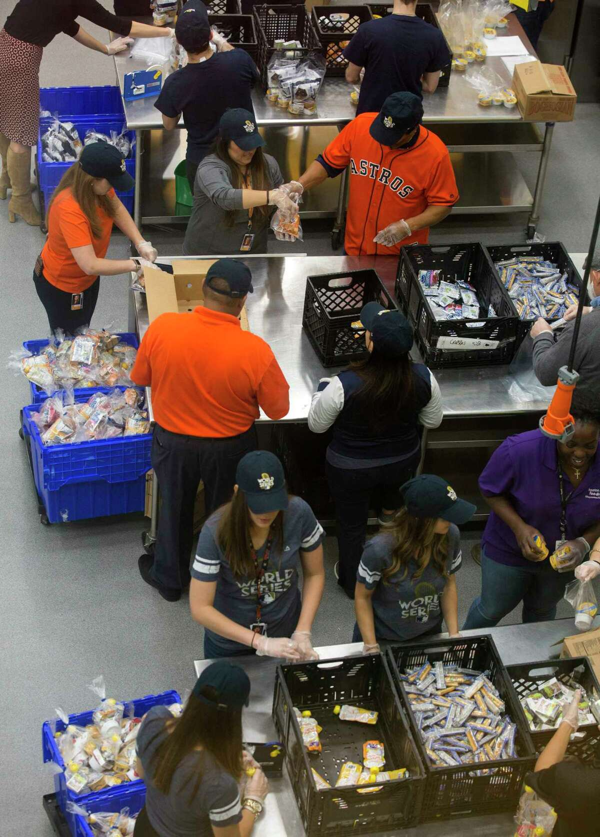 Houston Astros legend Jose Cruz, top right, and other volunteers help pack lunch bags at the Houston Food Bank Friday, Oct. 27, 2017, in Houston. ( Godofredo A. Vasquez / Houston Chronicle )