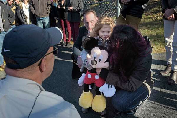 Jesse Harmon, left, his daughter, Drea Harmon, 3, center, and his wife, Nina Harmon, talk with Frank Squeo, founder of Baking Memories 4 Kids, who came to Drea's grandmother's house to surprise Drea with a trip to Disney World.  Drea has cystic fibrosis. (Paul Buckowski / Times Union)
