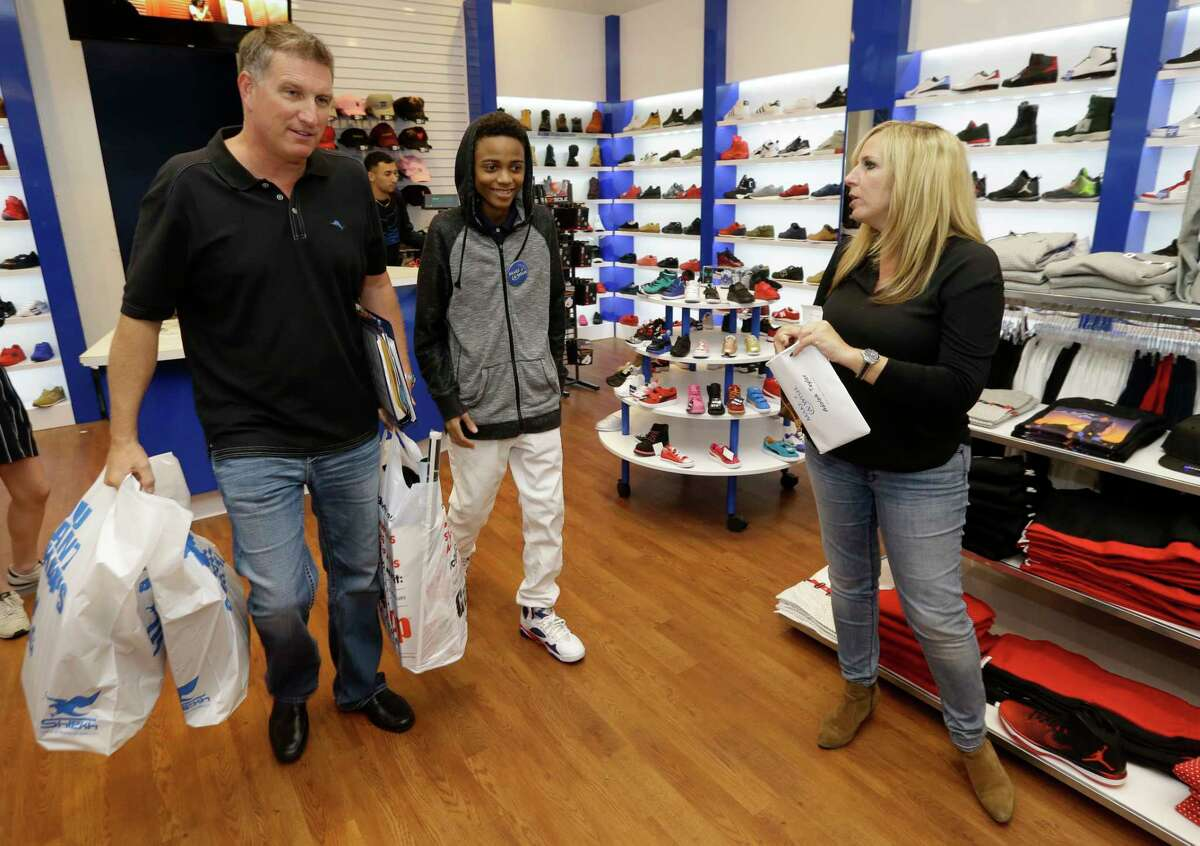 Make-A-Wish volunteers Erik Johnson, left, and Michele Wright, right, shop with Adolph Taylor at the Galleria Wednesday, Nov. 9, 2016, in Houston. ( Melissa Phillip / Houston Chronicle )
