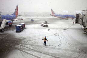 Southwest Airlines employees guide a plane into the gate at Midway International Airport in Chicago, Illinois, Tuesday, February 26, 2013. Several flights were canceled or delayed due to the winter storm. (Armando L. Sanchez/Chicago Tribune/MCT via Getty Images)