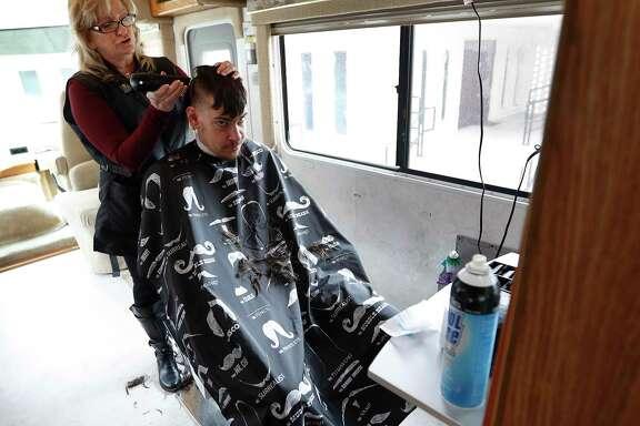 Barbara Goodson cuts Lawrence Campbell's hair in her mobile salon.    Barbara Goodson cuts Lawrence Campbell's hair in her mobile salon.
