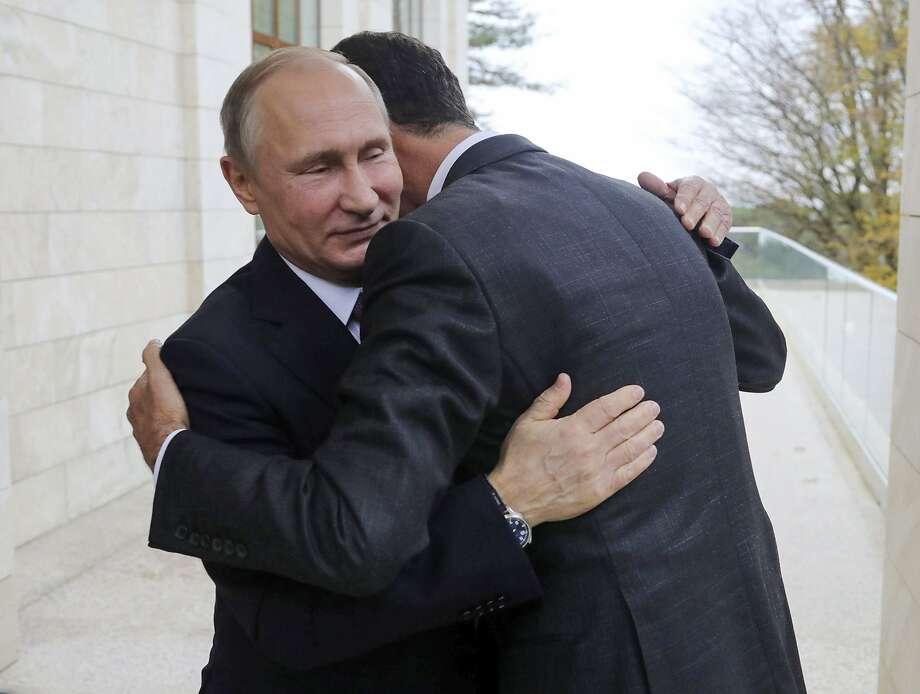 Russian President Vladimir Putin (left) hugs Syrian President Bashar Assad in the Black Sea resort of Sochi. Assad has ventured outside his nation twice since the conflict began in 2011 Photo: Mikhail Klimentyev, Associated Press