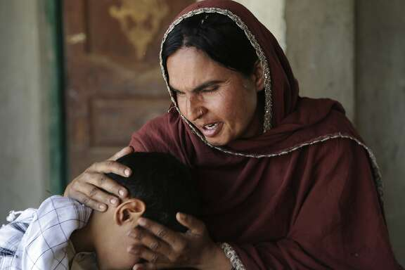 In this picture taken on May 4, 2017, Kausar Parveen comforts her child who was allegedly raped by a mullah or religious cleric, in Kehror Pakka, Pakistan. The Associated Press interviewed more than a dozen children or relatives of children who had been sexually assaulted by a maulvi or cleric at the madrassa where they studied. (AP Photo/K.M. Chaudary)