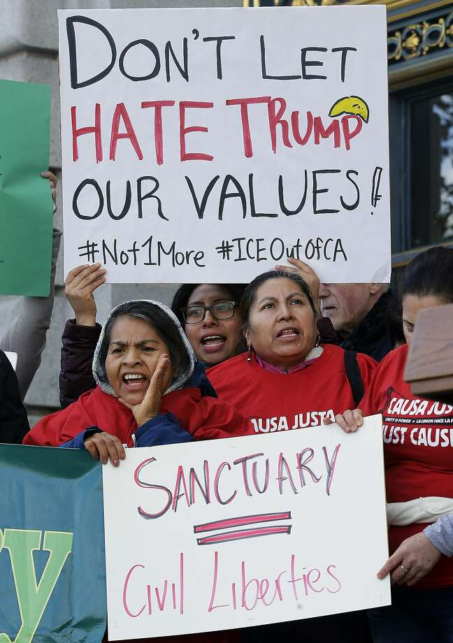 FILE - In this Jan. 25, 2017 file photo, protesters hold signs as they yell at a rally outside of City Hall in San Francisco. A federal judge Monday, Nov. 20, 2017 has permanently blocked President Donald Trump's executive order to cut funding from cities that limit cooperation with U.S. immigration authorities. San Francisco and Santa Clara County had filed lawsuits. (AP Photo/Jeff Chiu, File) Photo: Jeff Chiu, Associated Press