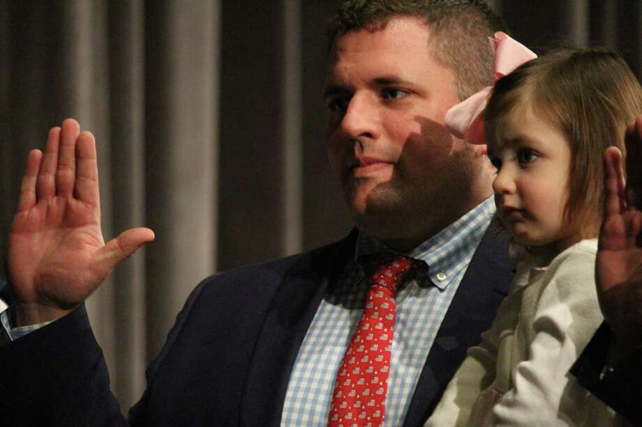 Representative Town Meeting member Frank Petise, R-10, holds daughter Elizabeth, 2, while he takes the oath of office Monday. Photo: Genevieve Reilly / Hearst Connecticut Media / Fairfield Citizen