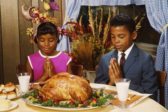 A boy and girl saying grace before a roast turkey dinner, circa 1970.  (Photo by FPG/Hulton Archive/Getty Images)