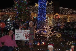 """The 2016 winning house of the Kingwood Civic Club Holiday Decorating Contest """"best lights"""" category gets a yard sign sponsored by RE/MAX Associates Northeast."""